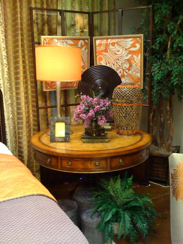 Lamp, floral, basket weave vase, & wood charger on a stand are all in scale with the large round bedside table