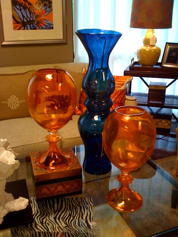 Colorful hand blown glass vases add drama to a rectangular glass cocktail table