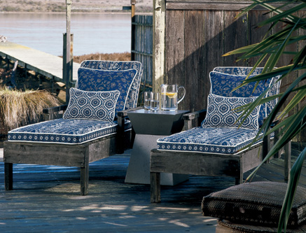 Traditional blue prints by Laura Ashley add color to these weather wood framed chaise lounges.